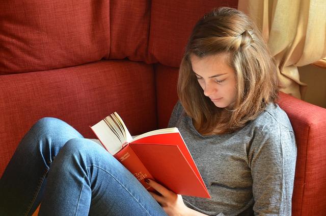 žena,kniha, červená sedačka