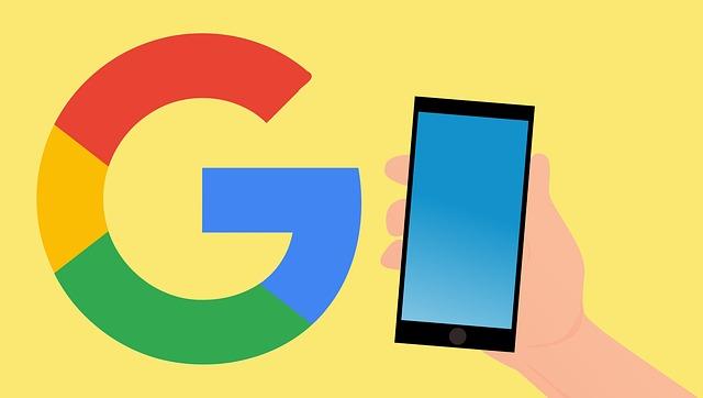 Velký symbol společnosti Google a mobilní telefon u něj